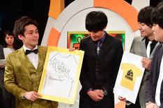 手描きのイラストでTシャツのデザイン案を披露する祇園・木崎(左)。