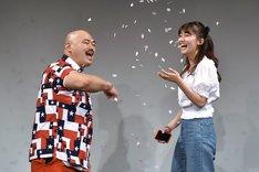 紙吹雪をまくクロちゃん(左)と、小嶋真子(右)。