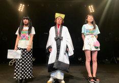 「やついフェスキャンペーンガール」グランプリを受賞した田中しろめ(左)と安藤きらり(右)に挟まれるエレキコミックやつい(中央)。