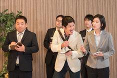 囲み取材に参加するゲスニックマガジンの記者・西条(ココリコ田中)ら。(c)NHK