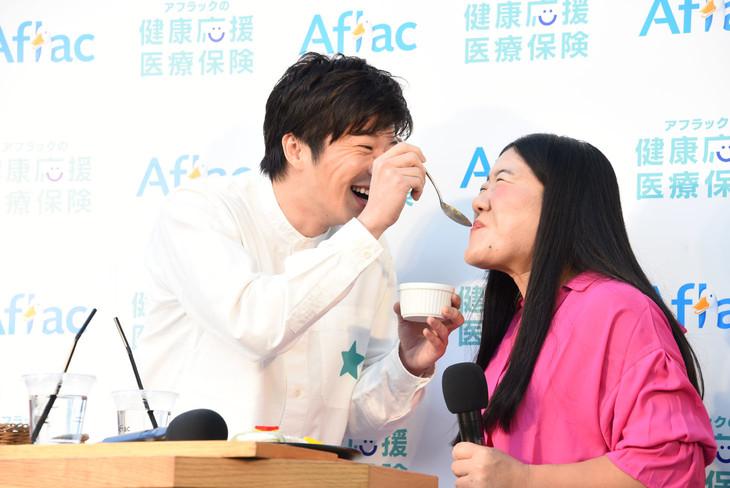 """田中圭(左)に""""激苦健康卵豆腐""""をあーんしてもらうガンバレルーヤよしこ(右)。"""