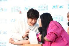 血圧測定の際、田中圭(左)を凝視するガンバレルーヤよしこ(右)。