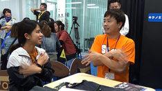 「異言語脱出ゲーム」で参加者に手話で話しかける次長課長・河本(右)。(c)MBS