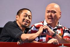 写真撮影の際、団長安田(左)が指でハートマークを作るよう求めて、クロちゃん(右)が渋々応じたワンシーン。