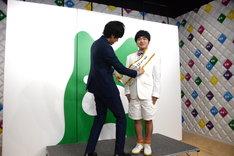 左から松田誠代表理事、アンバサダーのタスキをかけてもらう加藤諒。