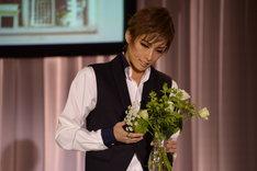 宝塚歌劇花組「Musical『ハンナのお花屋さん ─Hanna's Florist─』」制作発表会より。花を愛でる明日海りお。