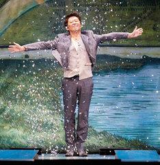 ステージいっぱいに金吹雪が舞い上がる劇中シーンを再現する、応援サポーターの坂上忍。