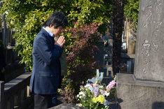 三遊亭円朝の墓に手を合わせる演出家の鵜山仁。