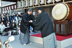 田中傳次郎(左)にばちを手渡す中村七之助(右)。