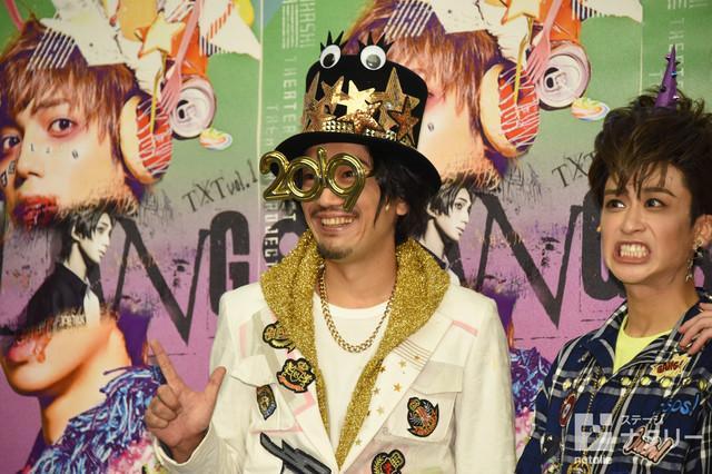 """""""2019""""と形取ったメガネをかけた谷口賢志(左)。"""