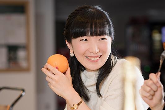 オレンジを手に持ち笑顔を見せる折笠富美子。