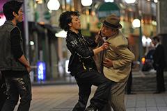 中尾彬演じるモキチは、通りがかる人に話しかけお金を騙し取る寸借詐欺師。路上で仕事をしているところを不良に見つかり、絡まれてしまう場面も。