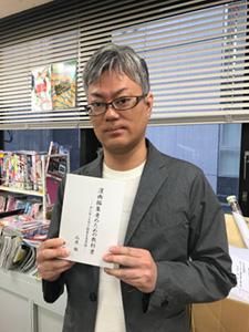 「漫画編集者のための教科書」を手にする武川新吾編集長。