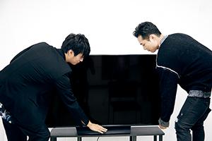 「4K液晶ビエラ FX750」の「転倒防止スタンド」機能を試す天野浩成(左)と八木将康(右)。