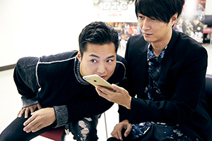 スマホの音声検索を試す八木将康(左)。