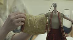 人形に衣装を着せる様子。