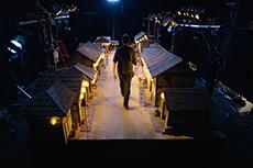 盆踊りの提灯が灯った村のセットを歩くスタッフ。