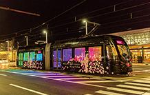 富山駅前を走る、ライトアップされた路面電車。写真は3月に実施された「アメイジングライト」のときの様子。