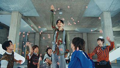 """「Jesus」MVより、メンバーに""""祝福""""されるタクヤ(中央)。"""