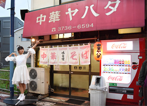 中華屋の前で回転する上田理子。