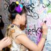 壁にサインを描く小鷹狩百花。