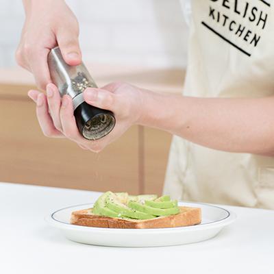 焼き上がったアボカドエッグトーストに黒胡椒を振る鬼龍院翔の手元。