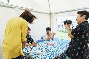 デジタル4Kビデオカメラでメンバーを撮影するカワクボタクロウ(右)。