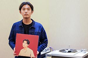 折坂悠太「平成」ジャケットのアナログレコードを手にする折坂悠太。
