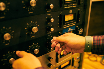 スタジオで機材を操作する保本真吾。