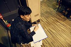 カンペを書く新野一孝氏。