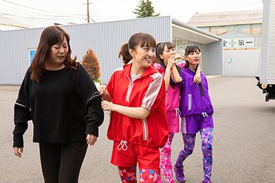 スタッフの服のジッパーを開ける百田夏菜子(左から2番目)。
