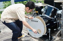 予備のドラムヘッドを取り付ける竹村郁哉(G)。