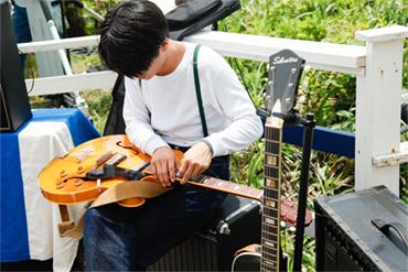 ギターの弦を張り替える角舘健悟(Vo, G)。