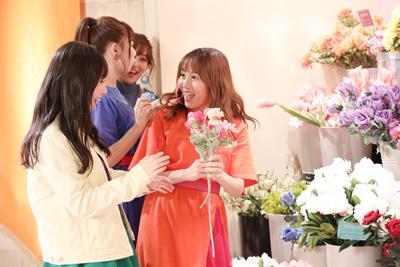 花を手に取り、弾けるような笑顔を見せる大場美奈。