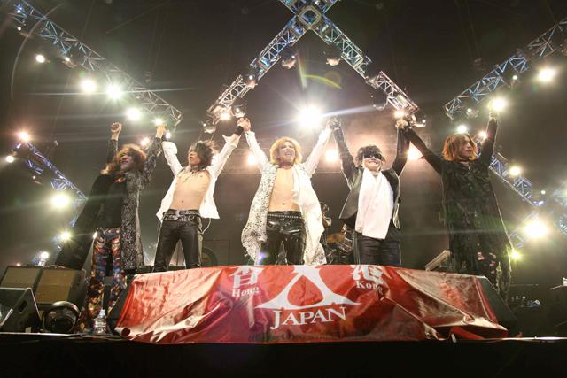 ステージ上で手をつないでバンザイをして盛り上がるX JAPANの画像