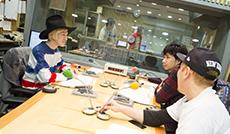 放送開始前に談笑する吉田山田と構成作家の奥田泰(手前)。