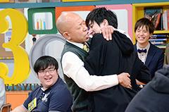 入学希望者を抱きしめるバイきんぐ小峠。