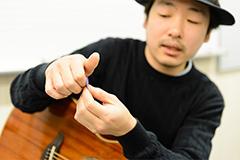 ANZEN漫才にピックの持ち方を教える小林圭吾先生。